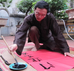 A brush with history: Le Thanh Hai, one of the village's famous calligraphers, displays his skills for tourists. — VNS Photo Hoai Nam